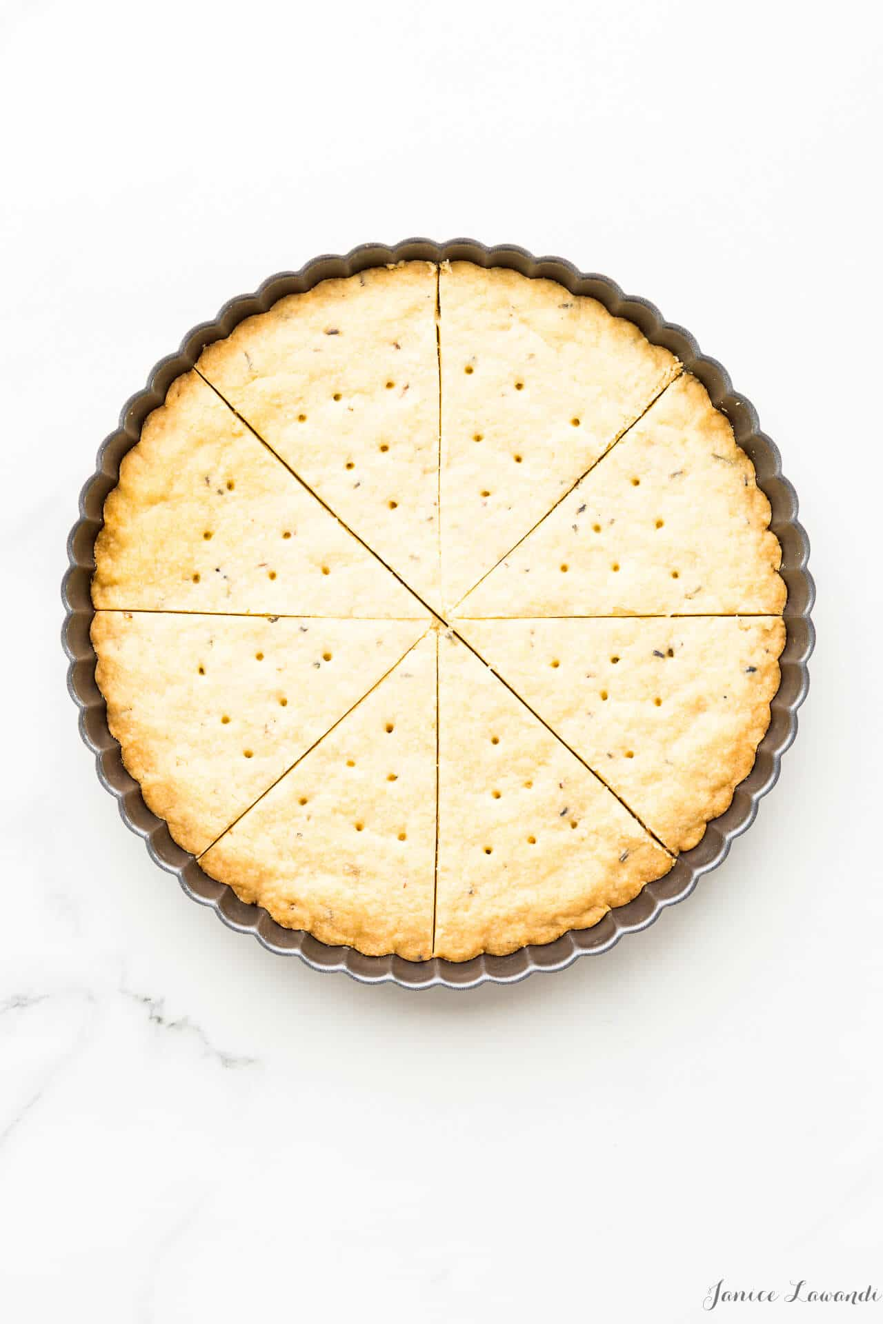 Press shortbread cookie dough into a tart pan with a crinkled edge, score, bake, and cut again for perfect triangle shortbread wedges
