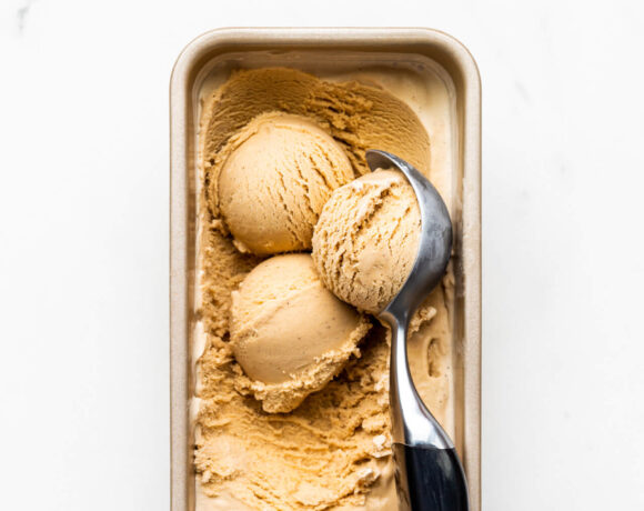 Scooping homemade black tea infused ice cream frozen in a loaf pan with a black handled ice cream scoop