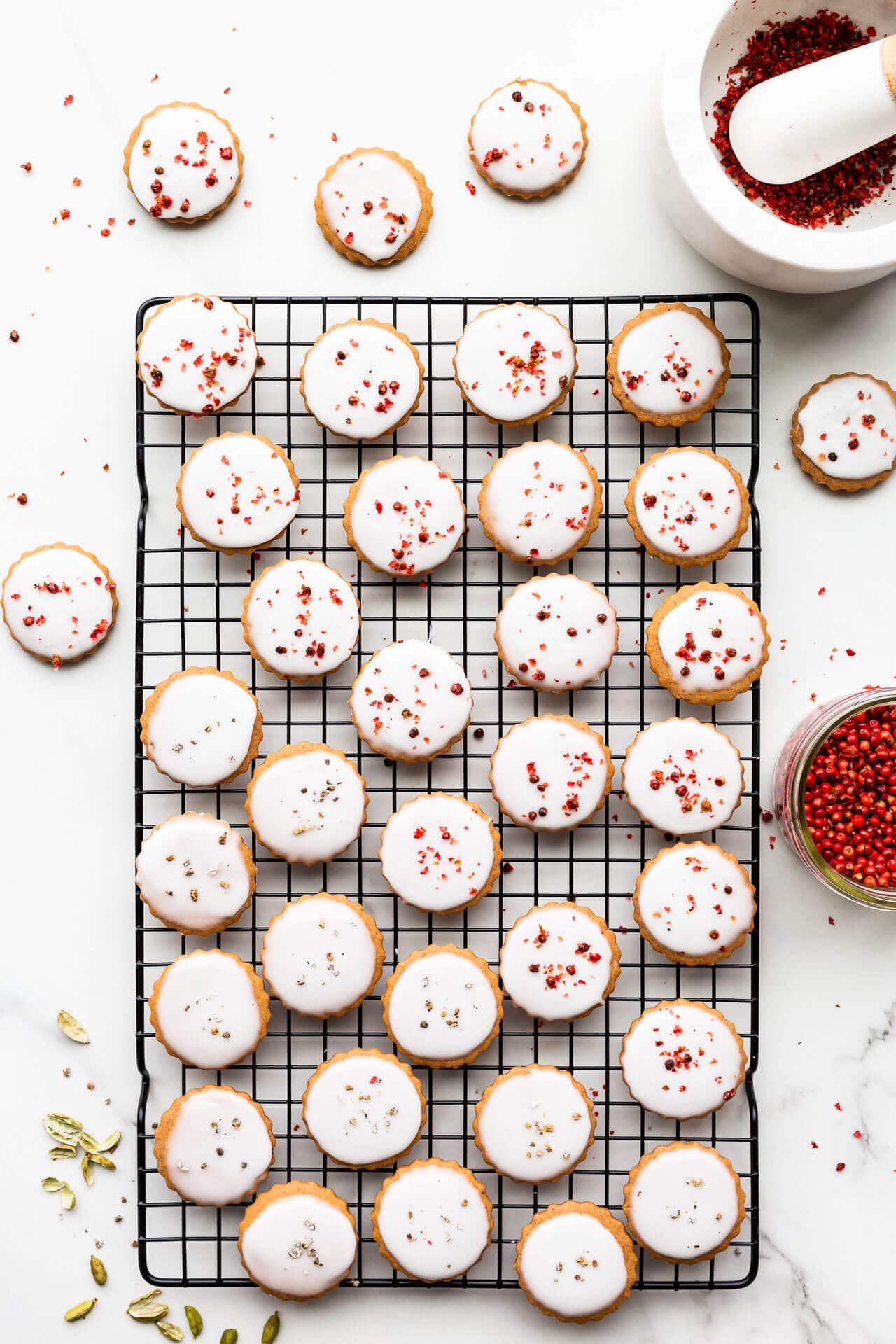 Glazed round gingerbread cookies garnished with crushed pink peppercorns and freshly ground cardamom on a black cooling rack.