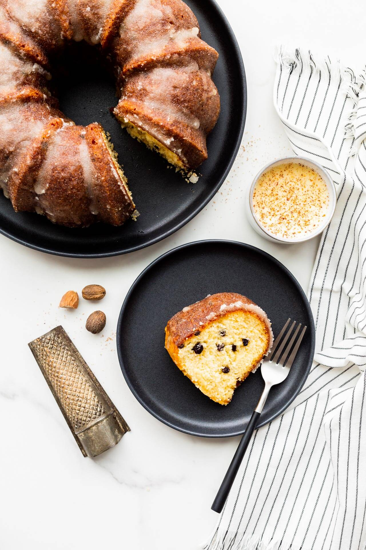 A slice of eggnog bundt cake with dried currants, served on black plate with a cup of eggnog and freshly grated nutmeg.