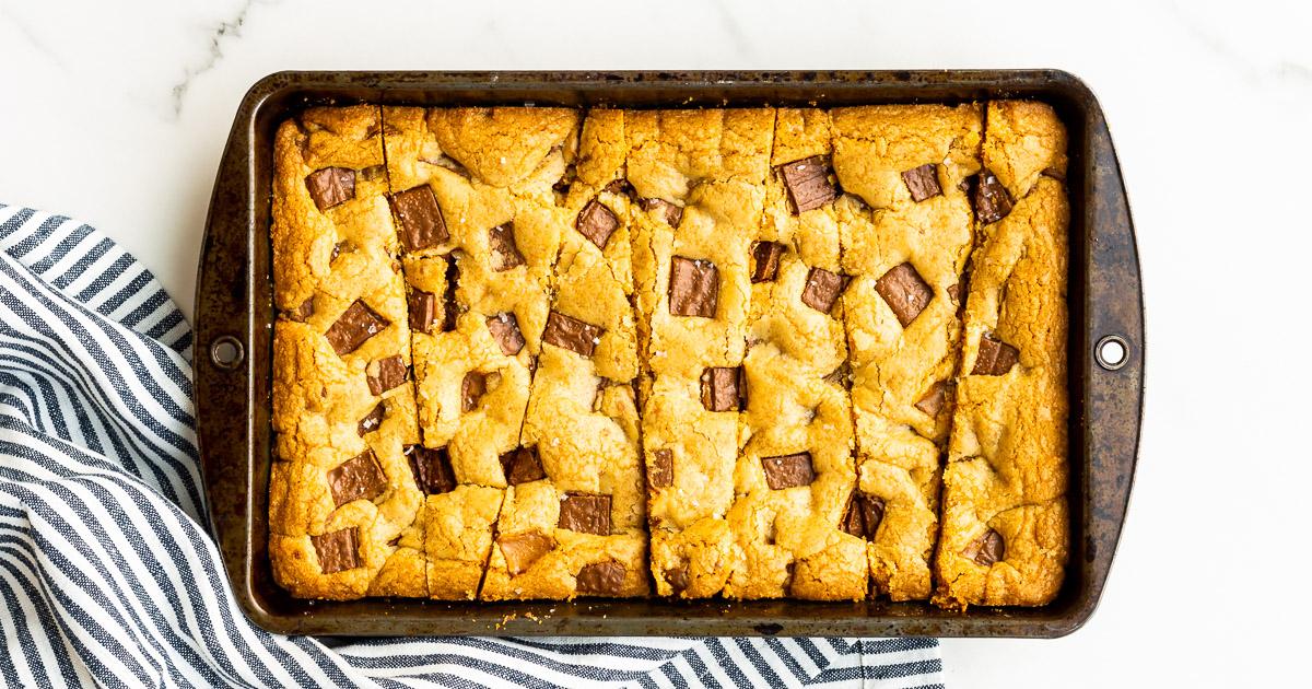 Skor cookie bars sliced into wedges in a 7x11 rectangular vintage baking pan