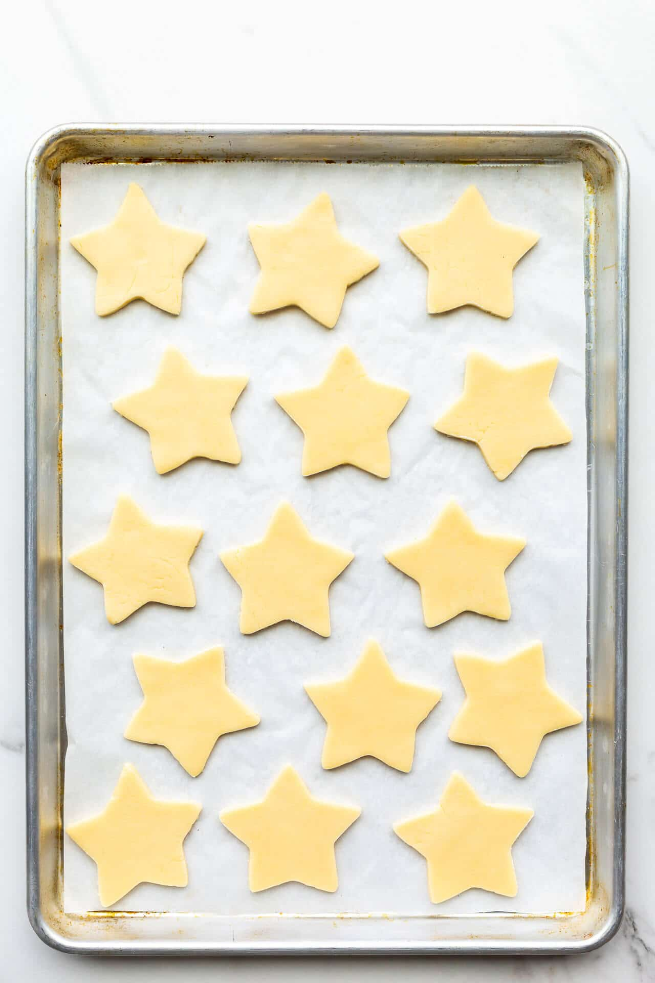 A sheet pan of cut out shortbread cookie stars ready to be baked.