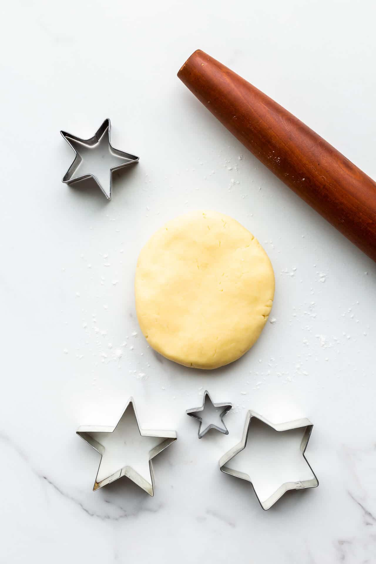 Shortbread dough with rolling pin and cookie cutters ready to be rolled and cut to bake them.
