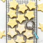 Star-shaped shortbread cookie on cooling rack with mini sifter of powdered sugar to sprinkle on top of the cookies