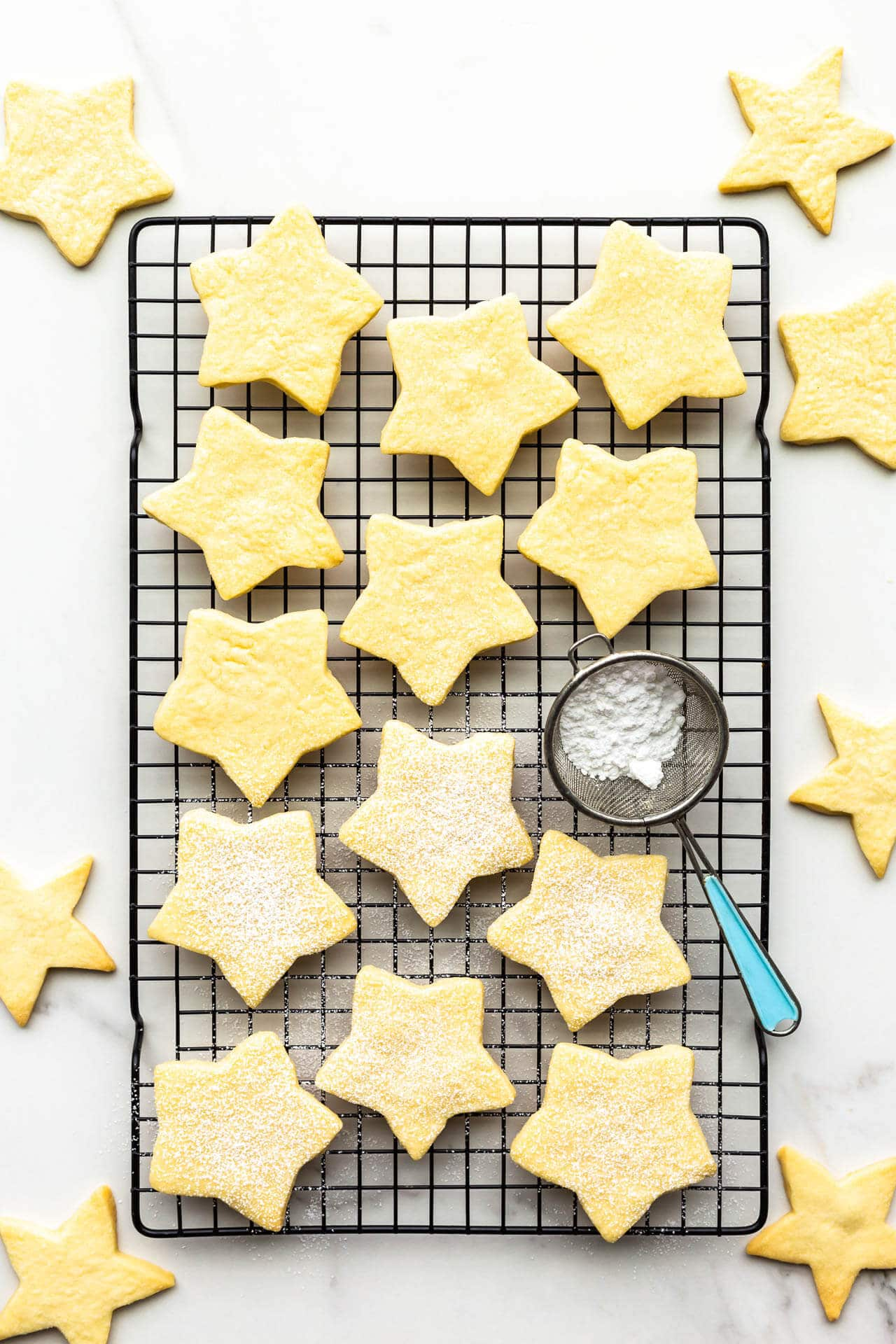 Star-shaped shortbread cookie on cooling rack with mini sifter of powdered sugar to sprinkle on top of the cookies.