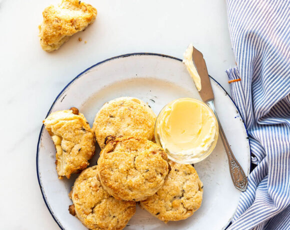 Baked lavender white chocolate scones on a blue-rimmed white enamelware plate with butter and a butter knife, blue and white striped napkin