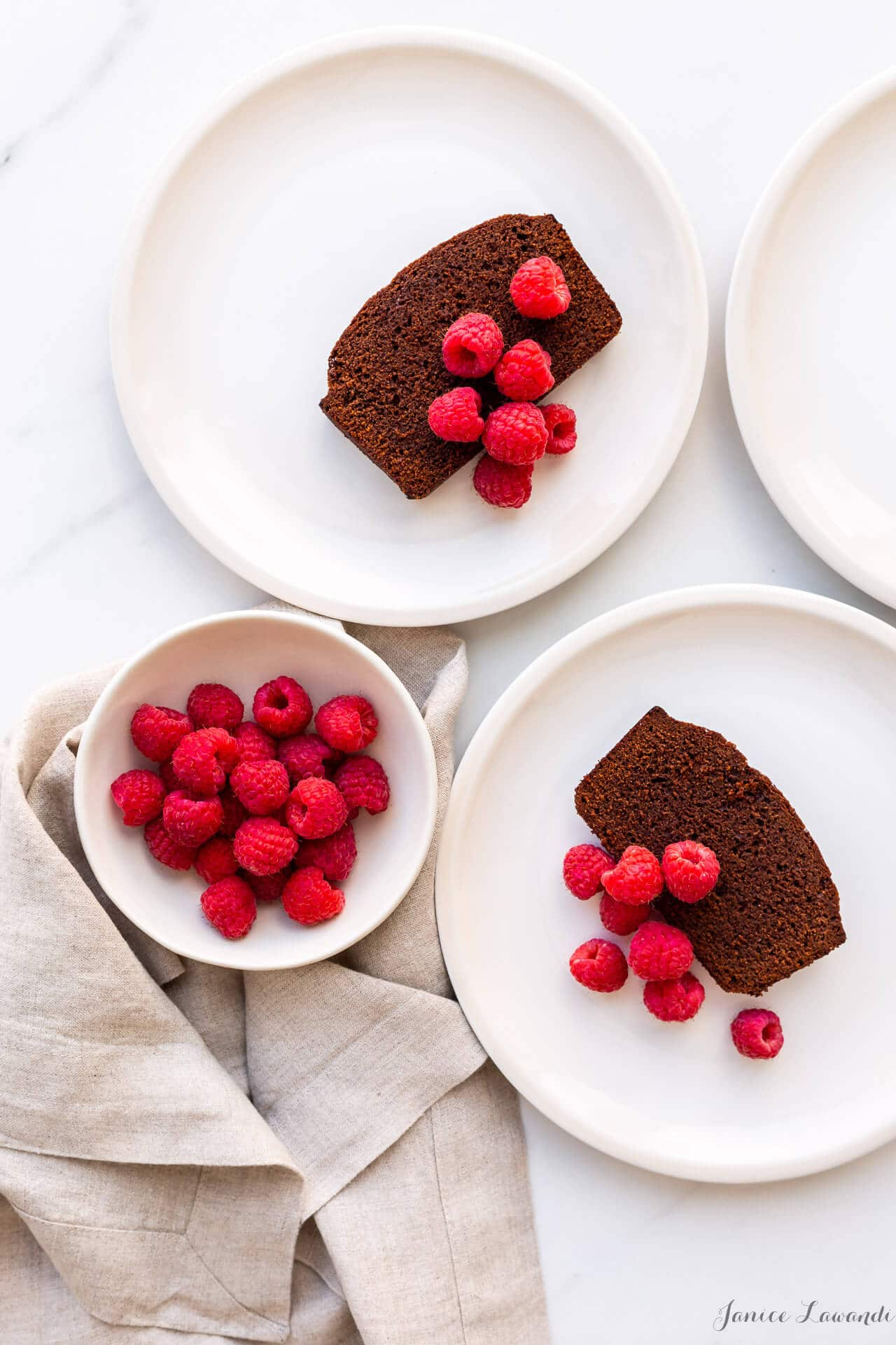 Slices of chocolate loaf cake served on cream coloured plates with a bowl of fresh raspberries