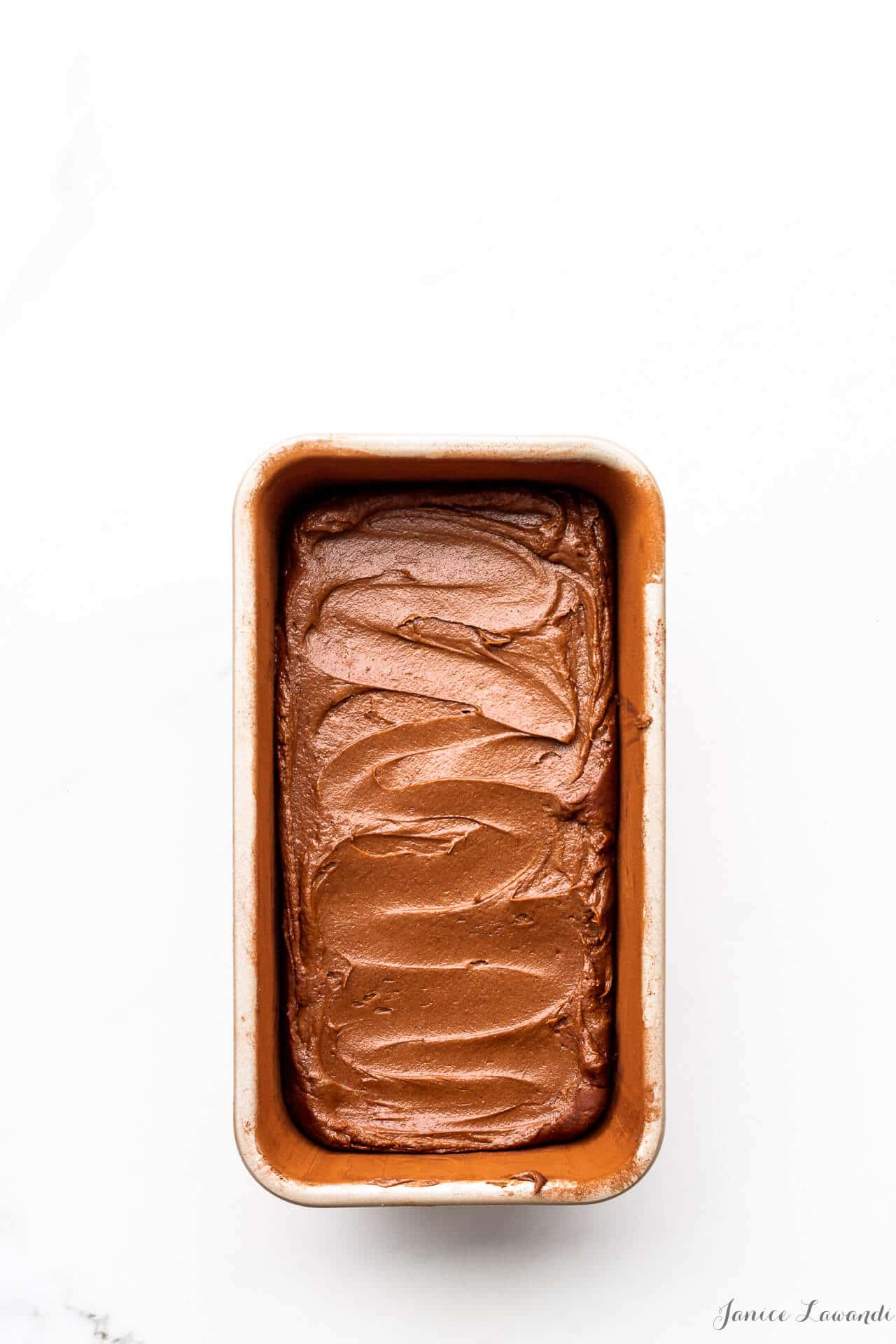 Chocolate cake batter swirled in a loaf cake pan that was prepared by buttering and dusting with cocoa powder to prevent the cake from sticking to the pan as it bakes