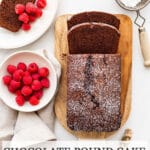 Chocolate pound cake sliced on a wood cutting board and served with a dusting of powdered sugar and fresh raspberries