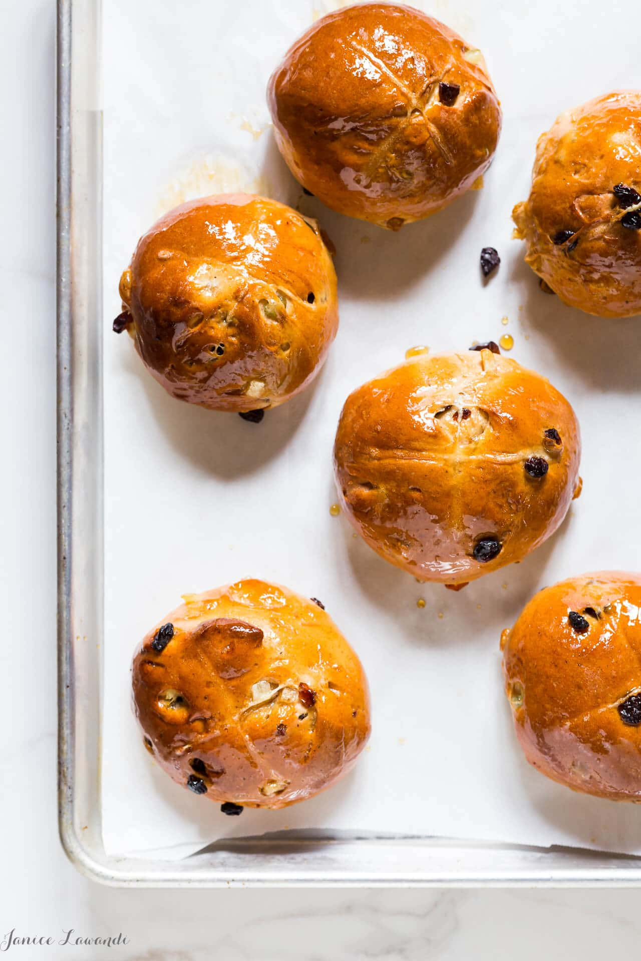 A baking sheet of round homemade hot cross buns with raisins and glazed with maple syrup