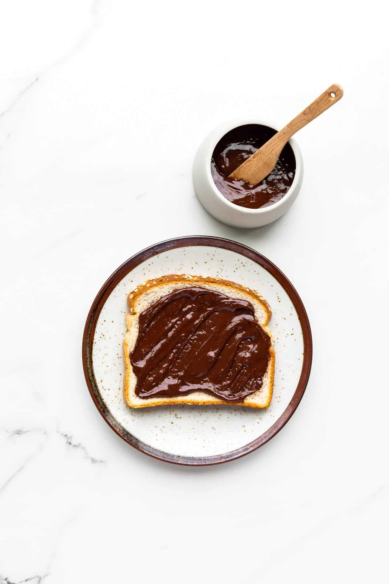 Nutella spread on white bread on a speckled ceramic plate with jar of homemade Nutella and wooden knife on side.