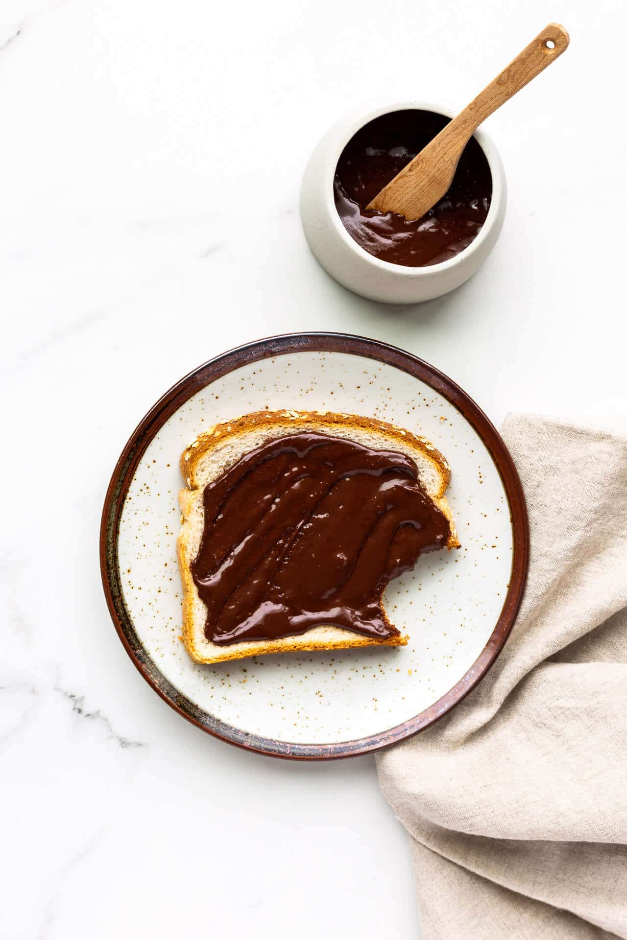 Chocolate peanut butter spread on white bread, with bite taken out. Set on a speckled ceramic plate with a beige linen napkin and a bowl of the spread with wooden knife.