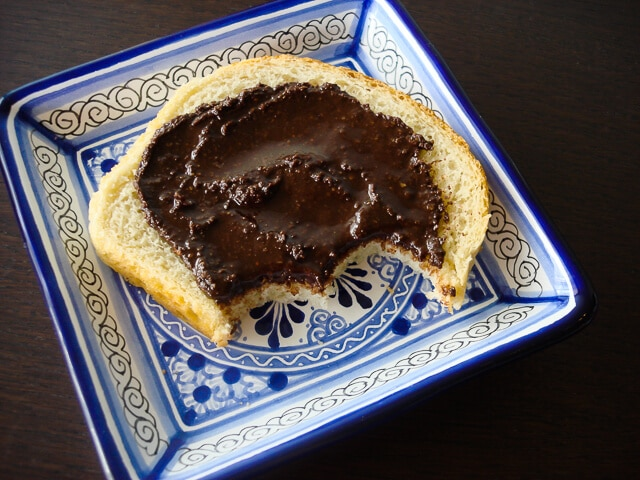 Homemade nutella on white bread with two bites taken out on a blue decorative square plate