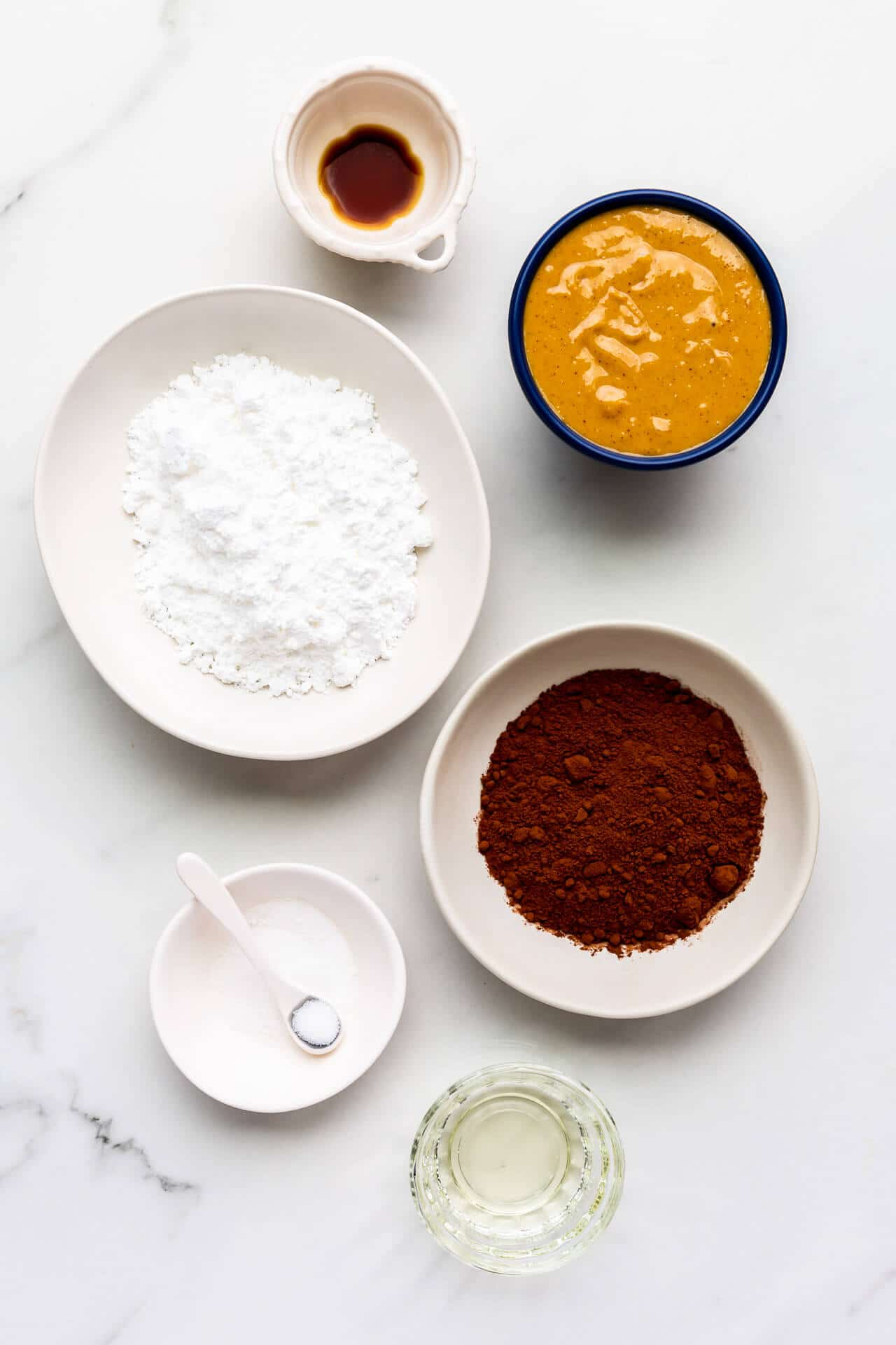 Ingredients to make homemade chocolate peanut butter spread include vanilla extract, peanut butter, powdered sugar, cocoa powder, salt, and a little canola oil.
