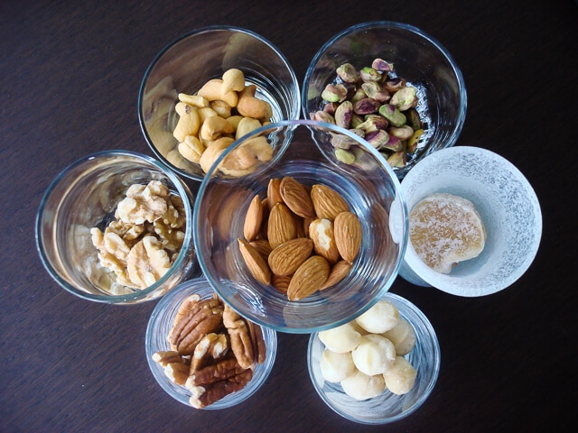 A variety of raw nuts in small glasses, almonds, walnuts, cashews, pistachios, macadamia nuts, pecans