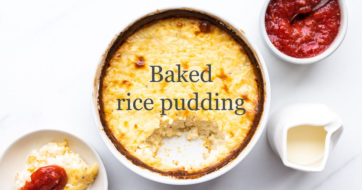 Baked rice pudding in a baking dish with dark golden brown edges with rhubarb compote and cream on the side