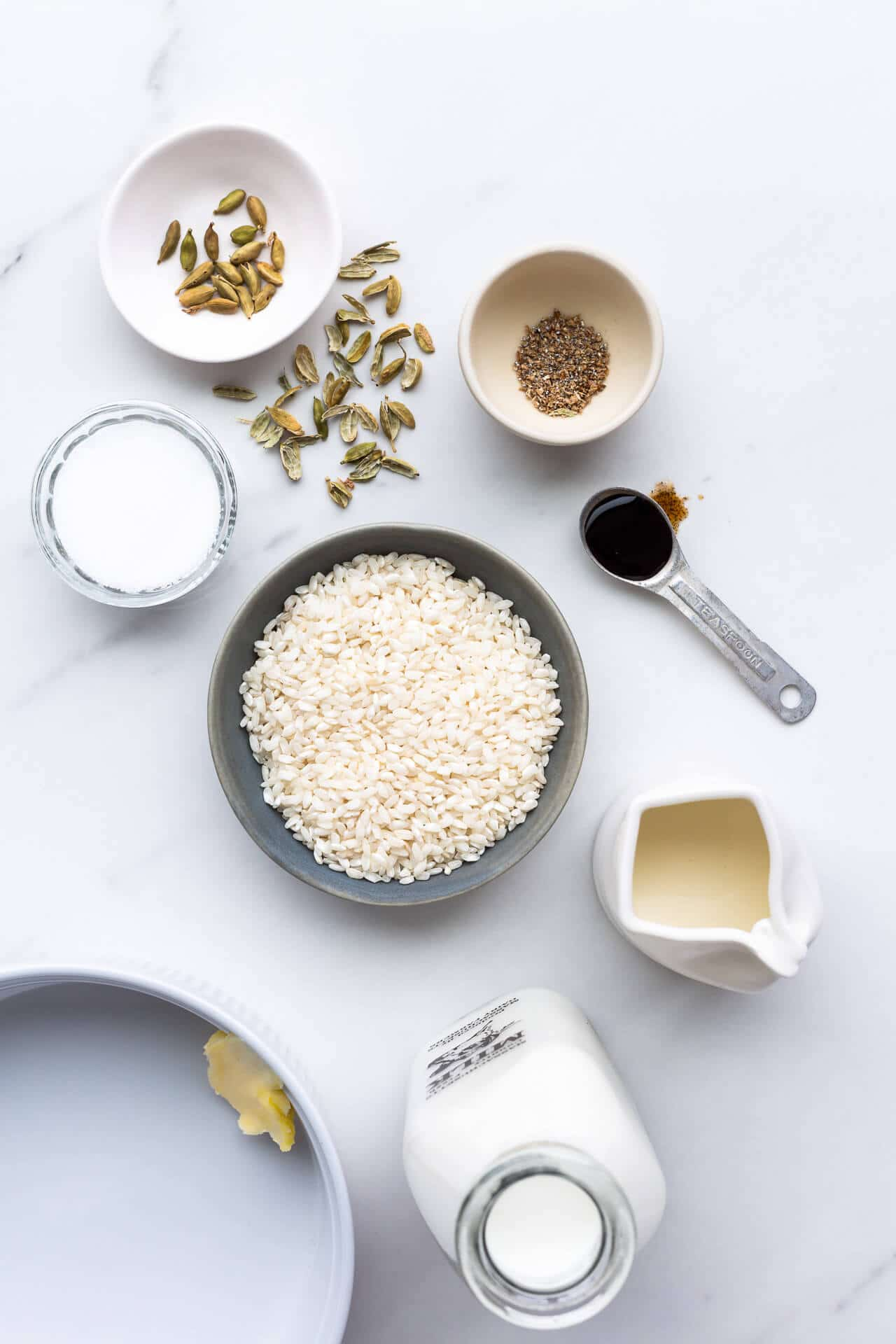 Ingredients for baked rice pudding laid out, including cardamom seeds, shelled and ground, vanilla bean paste, Arborio rice, sugar, milk, cream, and with a deep baking dish with a pat of butter on the side to grease it