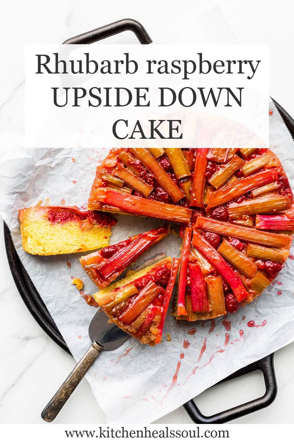 Rhubarb raspberry upside down cake on a parchment lined round black tray, cut into a few slices with a cake lifter under a slice