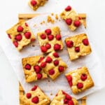 White chocolate and raspberry blondies cut into squares on a parchment-lined wood serving board
