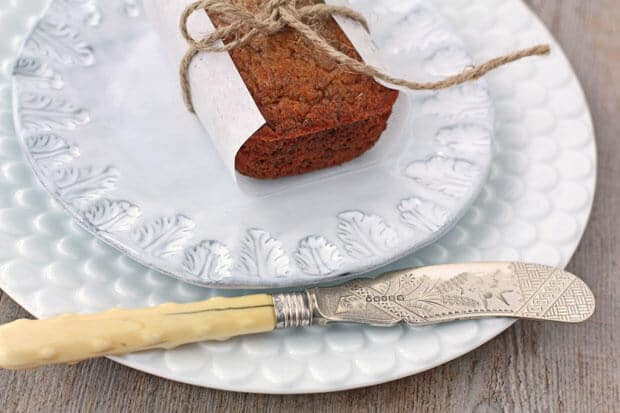 Mini Banana bread loaf wrapped in parchment and tied with string on light blue ceramic plate layered on white scalloped plate