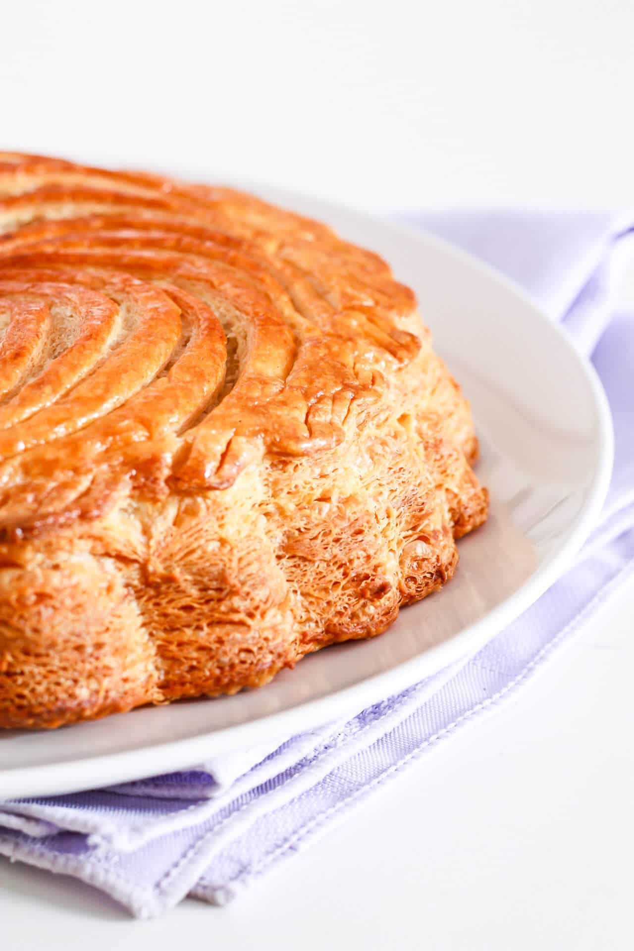 Galettes des rois (pithiviers) with a scalloped edge set on a white plate on a purple linen napkin