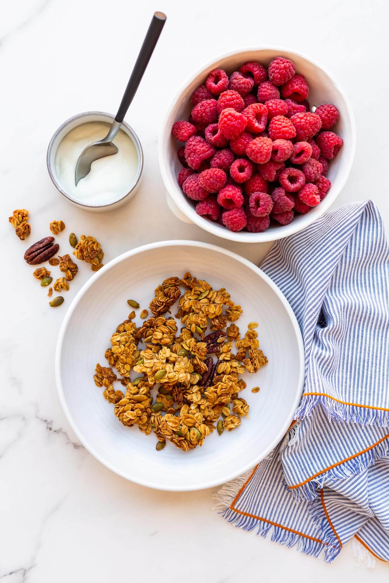 A bowl of granola clusters served with a bowl of berries and greek yogurt, striped linen napkin