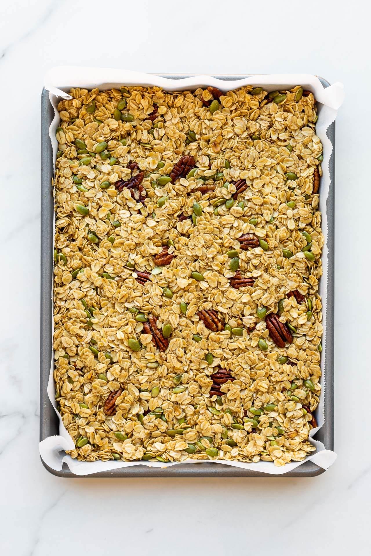Granola mixture pressed in a sheet pan