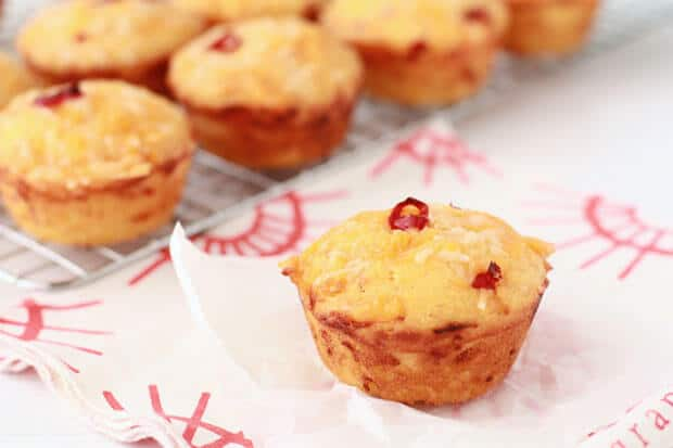 Chili cheddar cornbread muffins cooling on a cooling rack with one set on a square of parchment on red and white napkin
