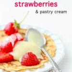 Crêpe with homemade vanilla pastry cream and fresh strawberries with a spoon of custard on a plate