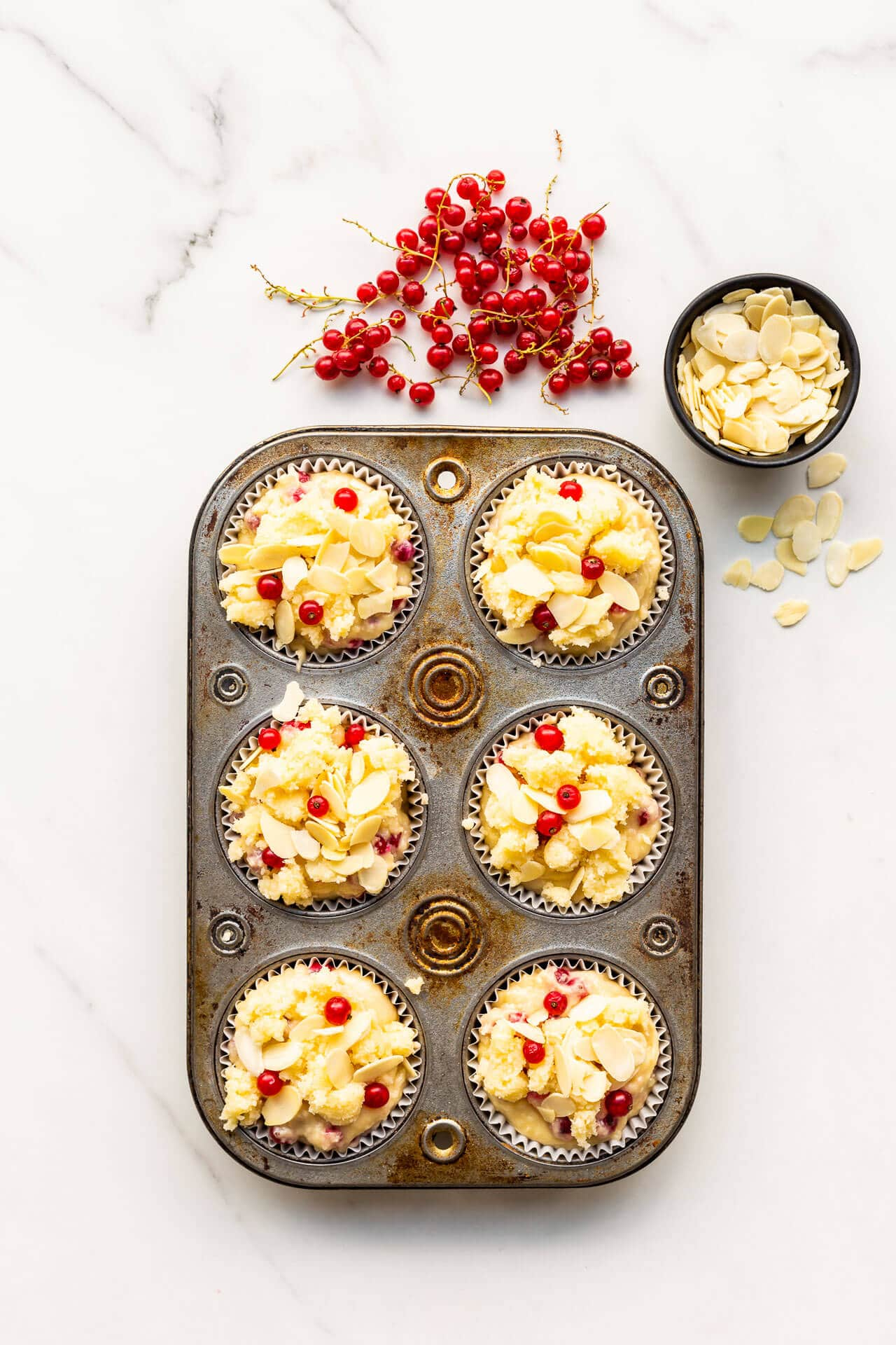 Making red currant muffins with a sugary crumble topping and sliced almonds on top