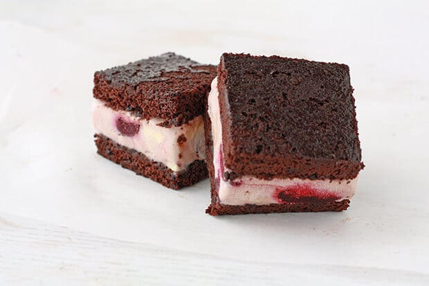 Two homemade ice cream sandwiches made with chocolate cake and cherry ice cream so you can see whole cherries in the ice cream layers