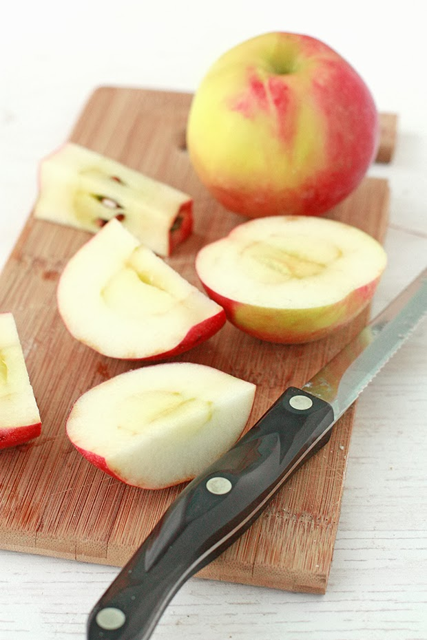 cut apples on a wooden cutting board with a serrated knife