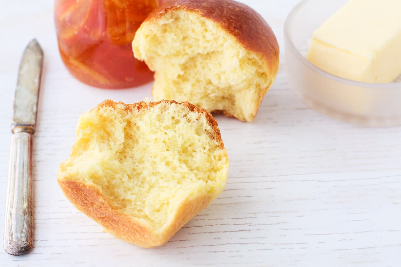 Homemade brioche brun split open to reveal a fluffy golden interior, served with butter and a knife