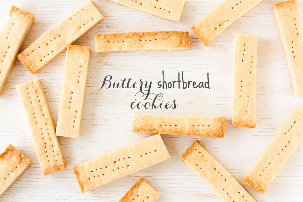 Buttery Shortbread cookies cut into bars like walker shortbread and arranged on a white-washed wood surface