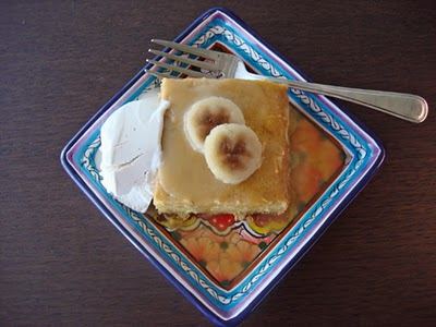 a square of banana cake with ice cream on a colourful square plate