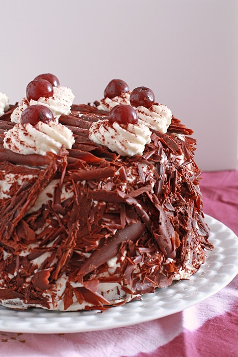 gâteau forêt noire coated in whipped cream and shaved dark chocolate, served on a white plate,