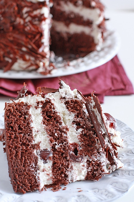 black forest cake sliced to show layers of chocolate sponge cake, whipped cream, and cherries
