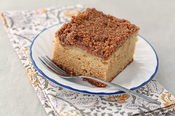 square piece of coffee cake on a white plate with blue rim on a floral napkin