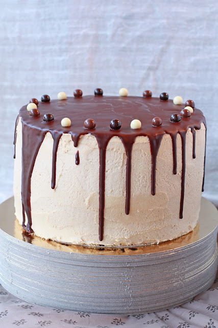 chocolate layer cake with coffee buttercream and dark chocolate drip with white, milk, and dark chocolate pearls on top