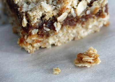 Side view of corner of date square to show layering of oat crumble on top and bottom with date paste in between