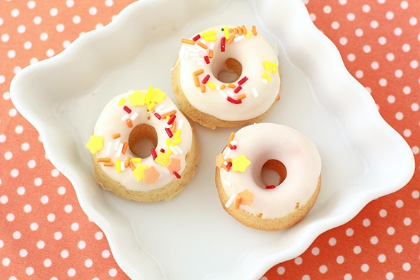 Mini pumpkin donuts with a white icing glaze and yellow, red, and orange sprinkles