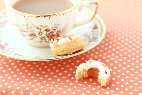 Baked pumpkin donuts and a cup of tea on an orange and white polka dot tablecloth