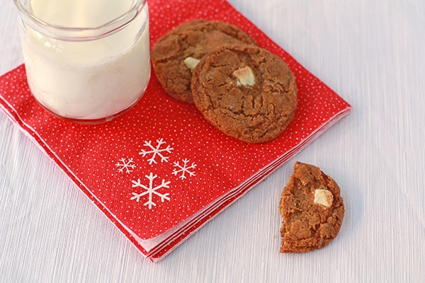 Gingersnap cookies on a red Christmas napkin with a glass of milk.