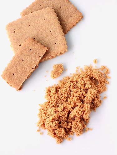 Homemade graham crackers with scalloped crinkle edges ground into homemade graham cracker crumbs
