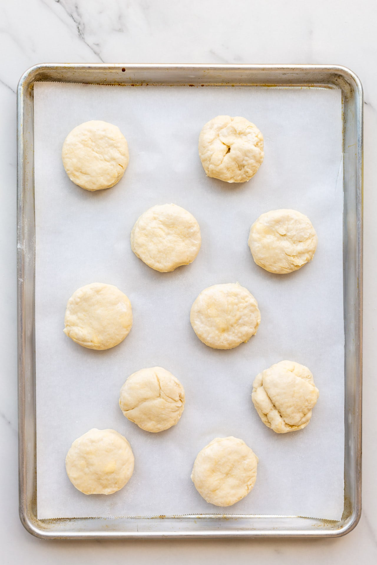Homemade biscuits on a parchment-lined baking sheet ready to be baked