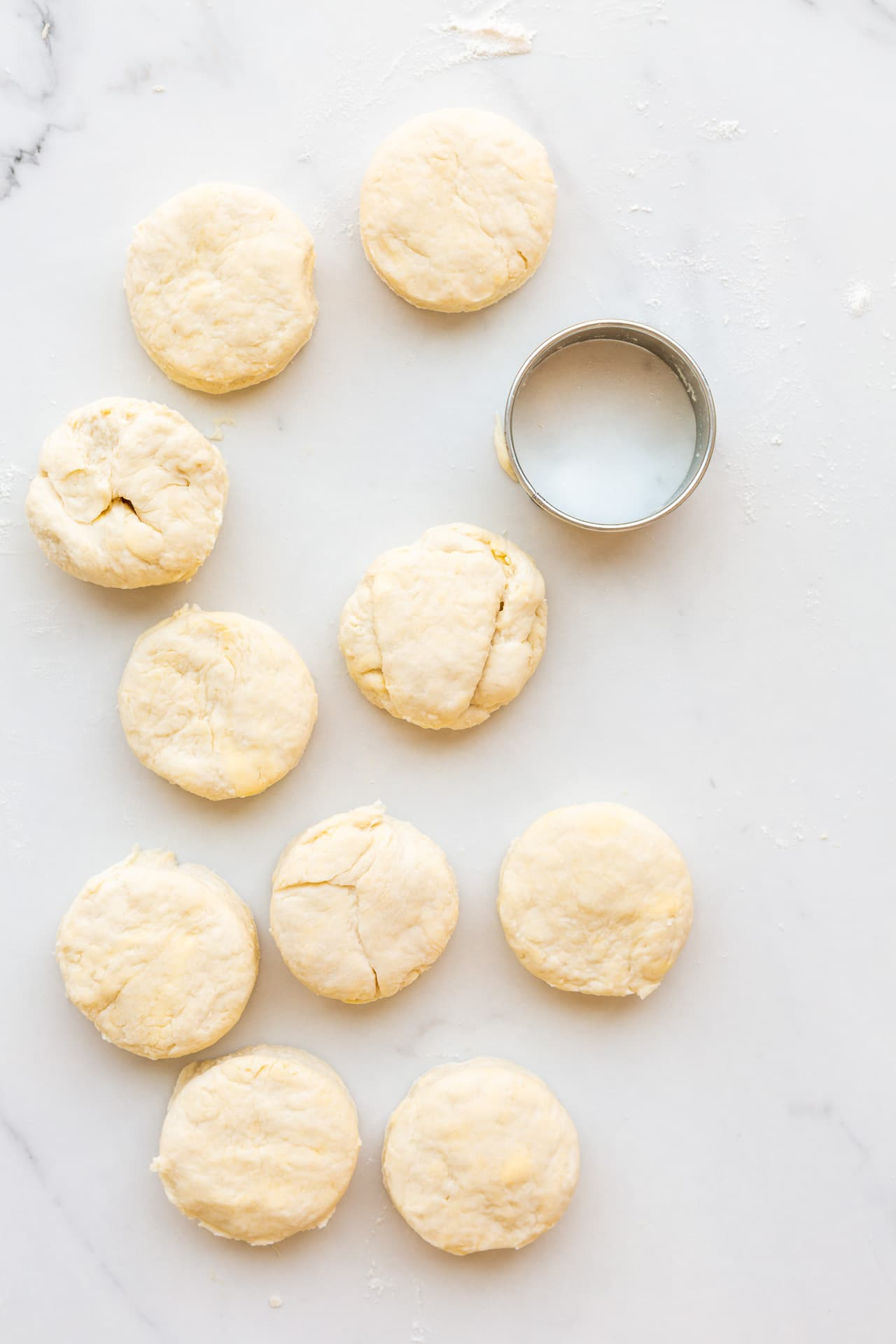 A round cookie cutter next to freshly cut homemade biscuits, ready to be baked