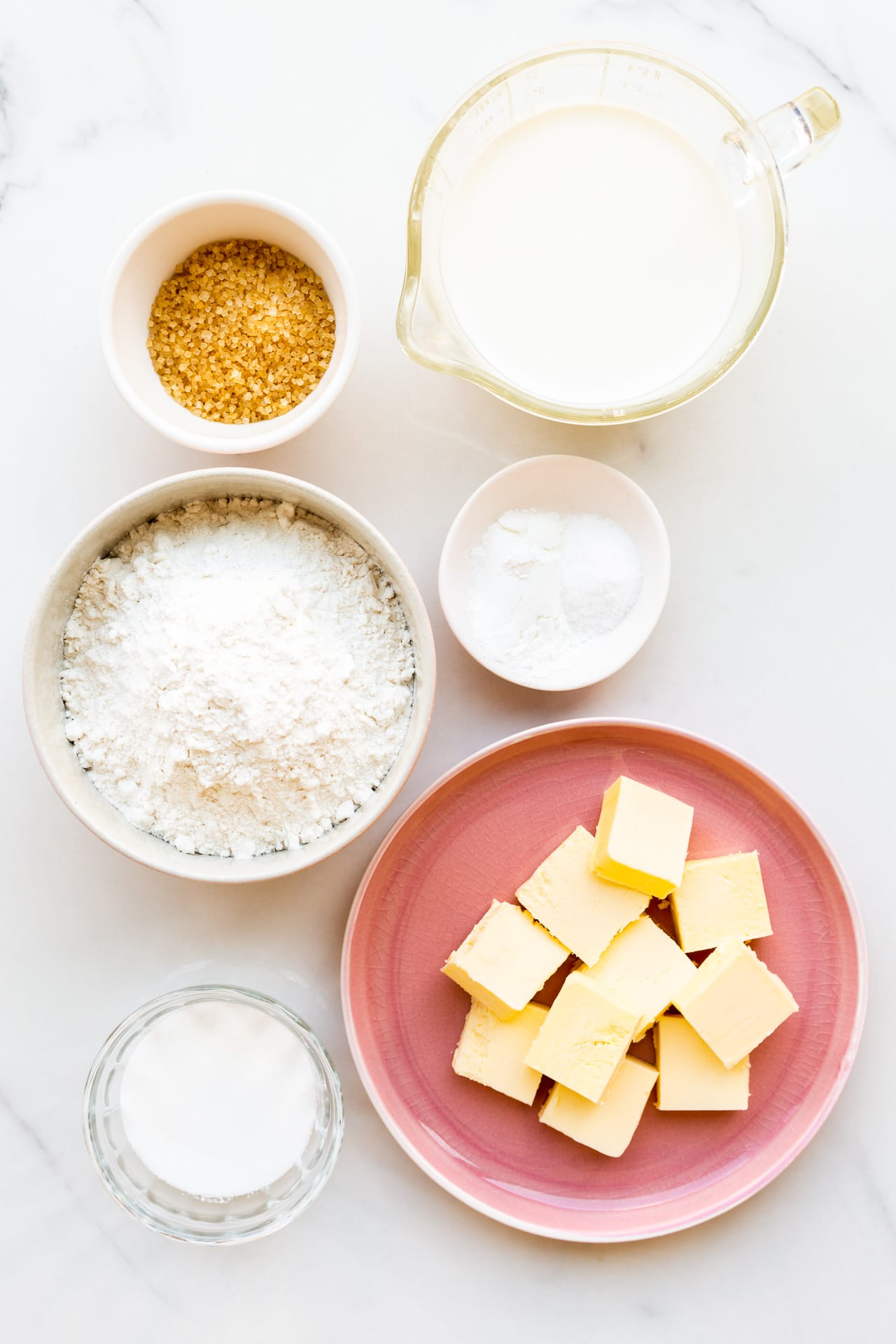 Ingredients for homemade biscuits measured out, including cubes of butter, sugar, salt, baking powder, flour, milk, and a little coarse sugar