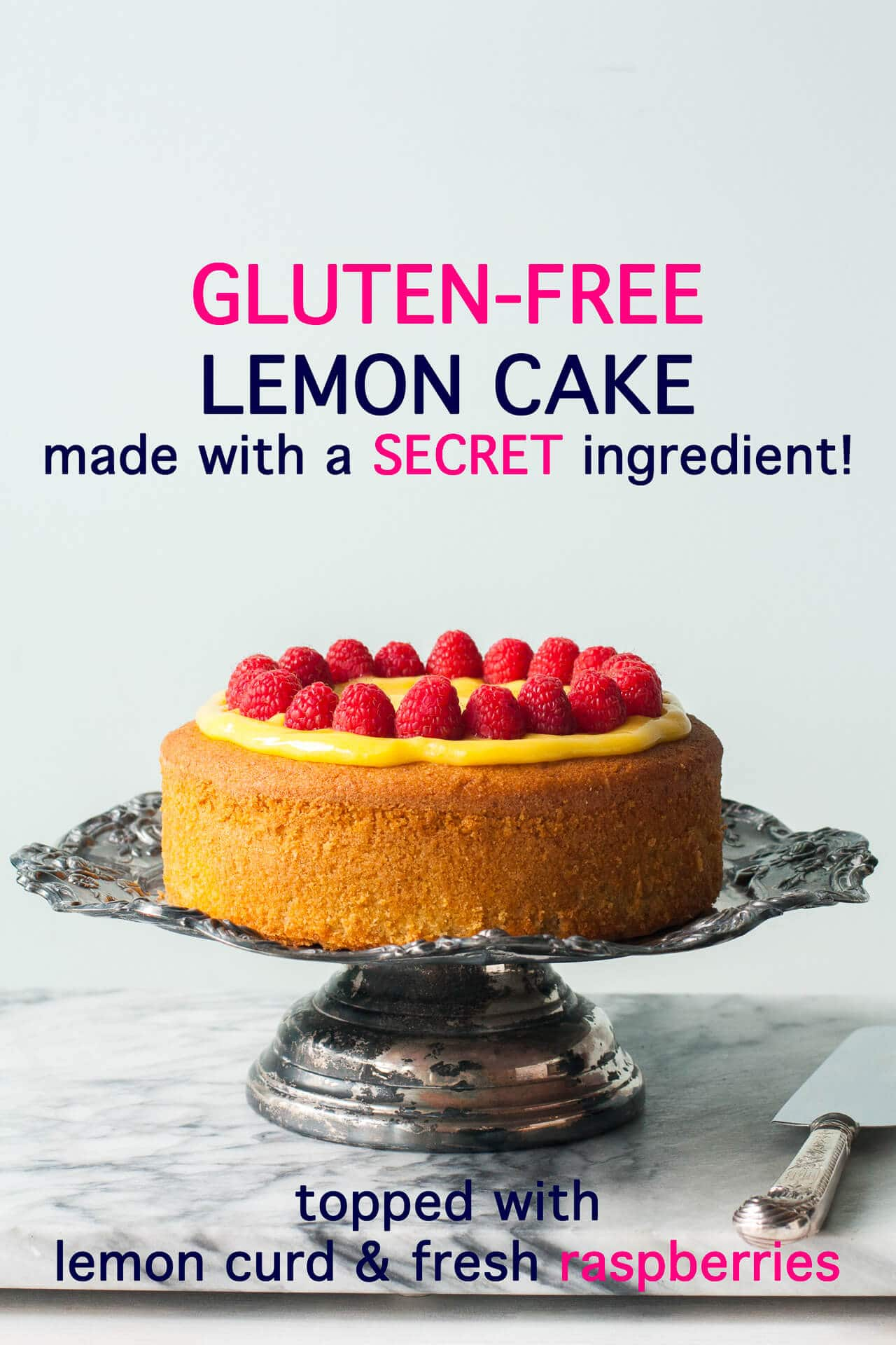 Single layer gluten-free lemon cake topped with homemade lemon curd and fresh raspberries served on a tarnished antique cake stand