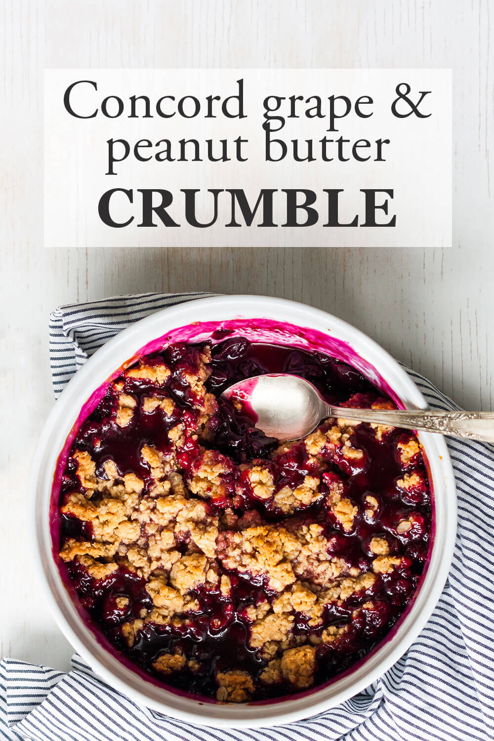 Concord grape cris with peanut butter crumble in a large white round baking dish with a silver serving spoon and a blue and white table linen
