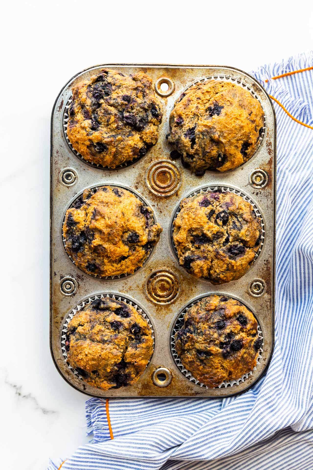 Baked blueberry bran muffins in a vintage muffin pan with a blue and white striped linen with orange edging